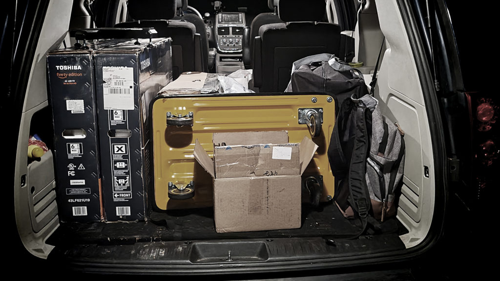 Van packed with various cargo, trolley, TV-s in boxes and backpacks